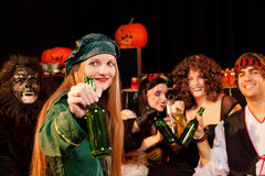 Party for carnival or Halloween. Group of young people celebrating a carnival or Halloween party in costumes drinking beer Stock Photography