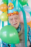 Party celebration.Senior man. Humourous elderly man at a party wearing a party hat and surrounded by crepe paper streamers and colorful balloons. Fun royalty free stock images