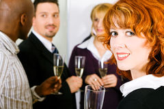 Party with champagne. Group of people having a toast or party with champagne standing together, one woman in front looking at the viewer Stock Photos