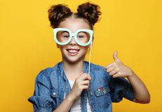Party, childhood and people concept: little girl with a paper accessories over yellow background. Party time stock image