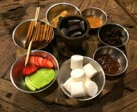 Party chocolate and caramel fondue with mamellow, brownie, biscuit, strawberry and apple on wood table Stock Image