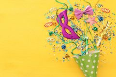Party colorful confetti and clown hat over yellow wooden background . Top view, flat lay. Party colorful confetti and clown hat over yellow wooden background royalty free stock photos