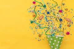 Party colorful confetti and clown hat over yellow wooden background . Top view, flat lay. Party colorful confetti and clown hat over yellow wooden background stock image