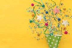 Party colorful confetti and clown hat over yellow wooden background . Top view, flat lay. Party colorful confetti and clown hat over yellow wooden background royalty free stock photography