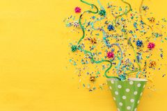 Party colorful confetti and clown hat over yellow wooden background . Top view, flat lay. Party colorful confetti and clown hat over yellow wooden background royalty free stock photo