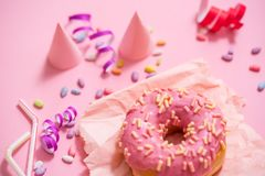 Party. colourful sugary round glazed donuts on pink background. Celebratory cap, tinsel, candy.  Stock Images