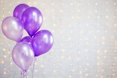 Party concept - air balloons over white brick wall background wi. Party concept - purple air balloons over white brick wall background with lights Royalty Free Stock Photos