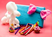 Party elements. party crafts. balloon dog, clay cupcakes, blue gift and balloons on bright pink background. Party concept. balloon dog, clay cupcakes and Stock Photography
