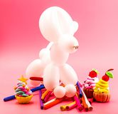 Party elements. party crafts. cute white balloon dog, clay cupcakes and balloons on bright pink background. Party concept. balloon dog, clay cupcakes and Stock Photo