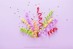 Party confetti explosion & opened envelope on violet card. Confetti explosion. Festive streamers coming out of an opened envelope on violet background. Party Royalty Free Stock Photos