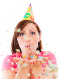 Party confetti woman. Party celebrating female isolated blowing confetti stock photo