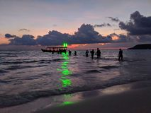 Party crowd wading back to boat towards green light from beach in Koh Rong, Cambodia stock photo