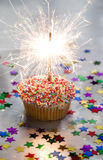 Party Cupcake. Cupcake with bright sparkler, on silver Royalty Free Stock Photo
