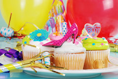 Party cupcakes. With hats and balloons in background Royalty Free Stock Image