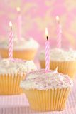 Party Cupcakes. With pink striped lit candles Stock Photography