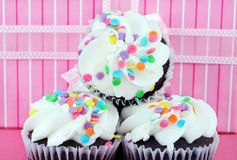 Party cupcakes in front of gift. Three party cupcakes, stacked, in front of a pretty gift box Royalty Free Stock Photography