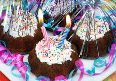 Party Cupcakes with Lit Candles. Brownie cupcakes decorated for a birthday with 2 lit candles, streamers and ribbons Stock Images