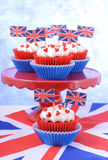 Party cupcakes with UK flags. Holiday party cupcakes with UK flags on red cake stand with Union Jack flag Stock Image