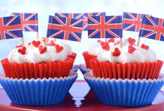Party cupcakes with UK flags. Holiday party cupcakes with UK flags on red cake stand with Union Jack flag Stock Photos