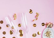 Party decor of golden color and champagne glasses on the pink background. Top view royalty free stock image