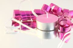 Party decoration. Pink and silver party decoration with pink candle on a mirror Stock Image