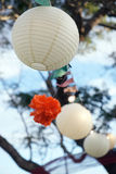 Party decoration. Chinese paper lanterns and orange pom pom decorations in outdoor garden party setting, flying in the wind Stock Image
