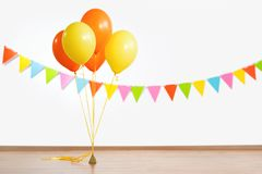 Colorful air balloons and flag garland. Party decoration concept - colorful air balloons and flag garland over white wall background Royalty Free Stock Photo
