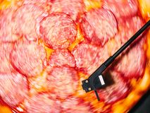 Party with delicious junk food. Italian pizza with salami sausage and cheese spinning on turntable vinyl player as vinyl royalty free stock image