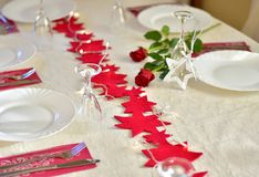 Party dinner table with red decoration. Place or table settings for party dinner or Valentine`s day or Christmas with red stars and red roses Stock Images