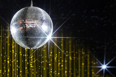 Party disco ball. With stars in nightclub with striped yellow and black walls lit by spotlight, nightlife entertainment industry stock image