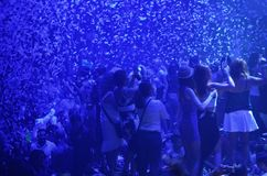 Party at disco with young people on the stage with blue lights and confetti rains. Royalty Free Stock Photos