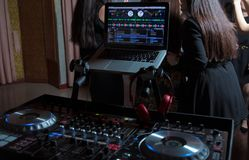 Party dj audio equipment on scene in club.Bright concert lighting.Disc jockey plays music show,mix tracks.Entertainment event in n. DJ's hands are busy mixing stock photo
