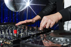 Party DJ in nightclub. DJ at dance party mixes track on sound mixer, nightclub with striped blue interior and silver disco ball with star, nightlife Stock Image