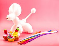 Party elements. party crafts. balloon dog, clay cupcakes and balloons on bright pink background. Party concept. balloon dog, clay cupcakes and balloons on bright Stock Photos