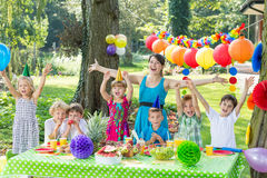 Party entertainer with children. Party entertainer and group of happy children during garden party royalty free stock photography