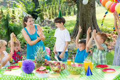 Party entertainer playing with kids. In garden, sitting beside table royalty free stock photos