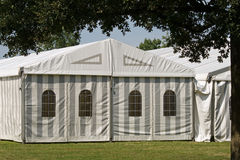 A party or event tent. A white party or event tent on a meadow in a public park Stock Image