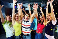 Party excitement. Photo of excited teenagers raising their arms in joy Stock Photos