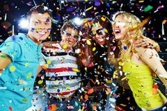 Party excitement. Photo of excited teenagers embracing at party under falling confetti Stock Image