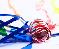 Party Favor. A close-up photo of a colorful party favor and streamers on a white background Royalty Free Stock Photos