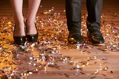 At the party. Feet of couple standing on club floor with confetti stock photo