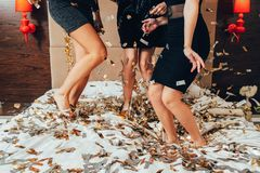 Party females fun joy confetti women black. Party females. Fun and joy. Glitter confetti. Young women in black dancing on bed. Festive mood and decor. Legs royalty free stock photos
