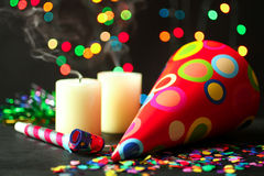 Party, festive hat and confetti. Festive hat and candles on Background of Christmas lights garlands Stock Image