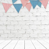 Party flags hanging on brick wall and perspective white wood bac Stock Images