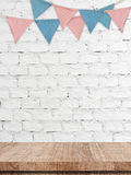 Party flags hanging on white brick wall and wood table backgroun Royalty Free Stock Photography
