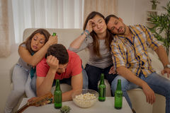 After Party. Four young friends drunk and hungover after house party sitting on the couch royalty free stock photography