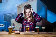 Party girl. Beautiful girl drinking beer. brunette girl toasting and eating in the pub stock images