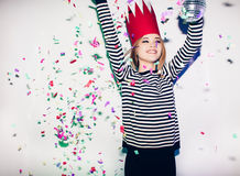 Party girl in colorful spotlights and confetti smiling on white background celebrating brightful event, wears stripped Stock Images