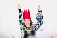 Party girl in colorful spotlights and confetti smiling on white background celebrating brightful event, wears stripped. Party girl in colorful spotlights and stock photography