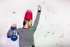 Party girl in colorful spotlights and confetti smiling on white background celebrating brightful event, wears stripped. Party girl in colorful spotlights and royalty free stock photography